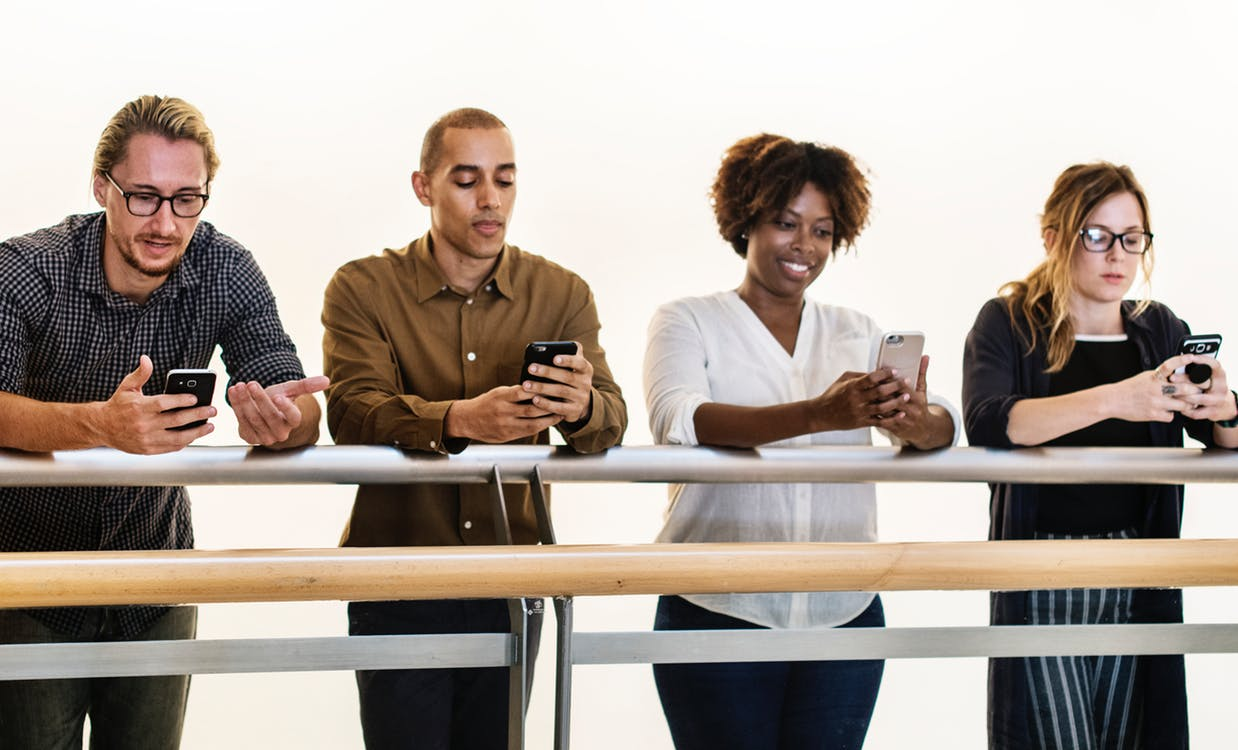 Input Image of four people looking at phones